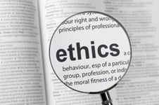 Magnifying glass focused on the word ethics.